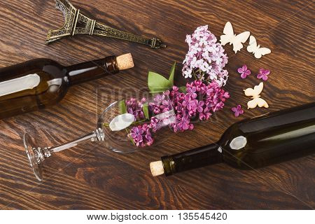 Wineglass with lilacs miniaturized Eiffel tower bottles and butterflies decorations on the wooden background