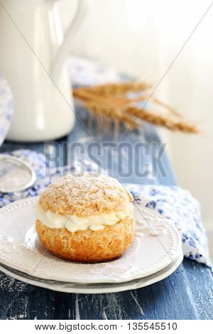 one choux pastry stuffed with cream on two white saucers on a blue wooden background