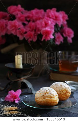 Two custard pastries stuffed with cream on glass saucer on a dark background in the background - azalea flowers