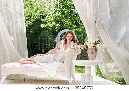 Pretty woman having fun in the summer garden gazebo. Opulent outdoor living area with flowers for outdoor celebration wedding or tea party.