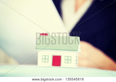 Business woman with small house.