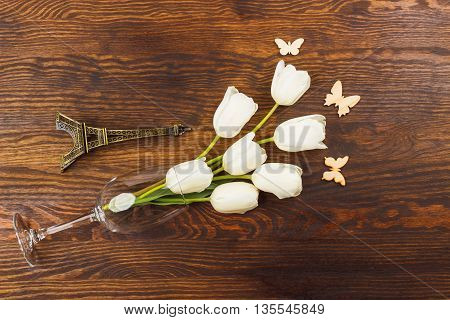 Wineglass with bouquet of white tulips and miniaturized Eiffel tower on the wooden background