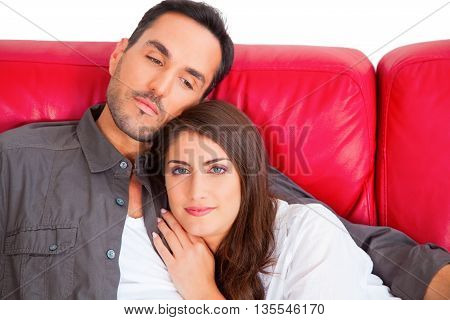Portrait of beautiful young woman with boyfriend. Loving couple relaxing on red sofa. They are spending leisure time isolated over white background.