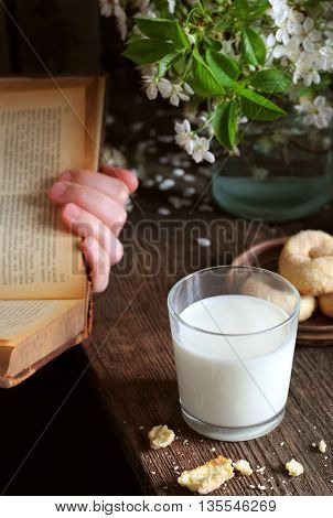 milk in a glass on a wooden table a girl reading a book spring season