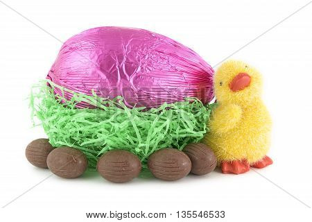 toy chick and chocolate easter eggs in nest isolated on white background