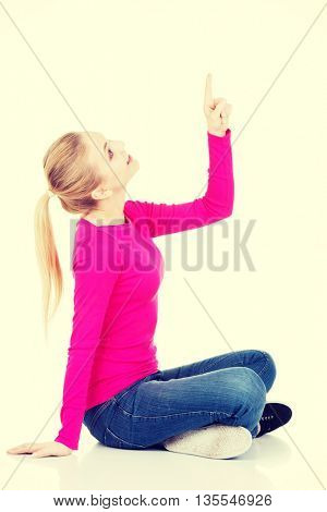 Young beautiful casual woman pointing up.