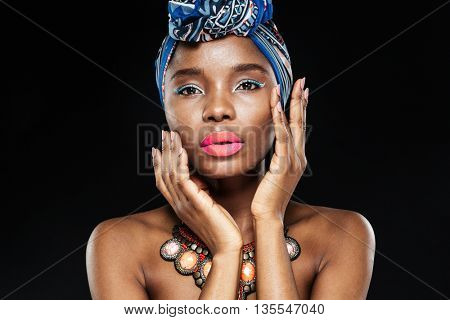 Close up portrait of an african american female fashion model posing with hands by face isolated on the black background