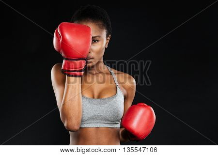 Strong intense young fitness woman covered her face with boxing gloves over black background