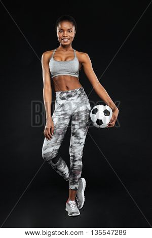 Full length portrait of a smiling sports woman posing holding football isolated on a black background