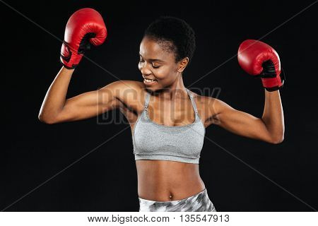 Portrait of a smiling fitness woman standing with boxing gloves in victory pose isolated on a black background
