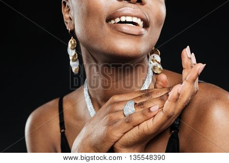 Cropped image of a beautiful attractive african woman isolated on the black background