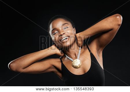 Portrait of a smiling beautiful african woman posing with eyes closed in studio isolated on the black background