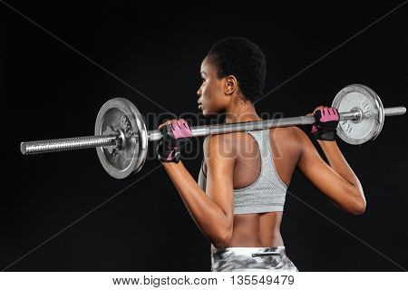 Strong young woman with beautiful athletic body doing exercises with barbell isolated on a black background