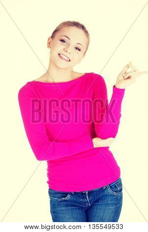 Young casual woman pointing aside.