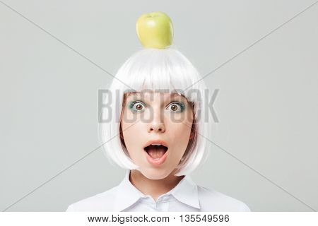 Pretty amazed young woman put apple on her head