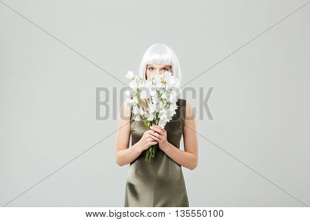 Pretty young woman in blonde wig covered her face with bouquet of flowers
