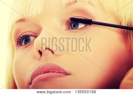 Close up on beautiful young woman doing make up on eyelashes.