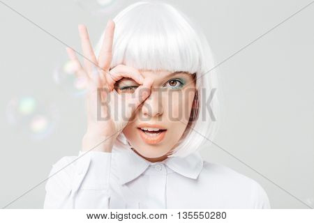 Playful charming young woman looking through her fingers