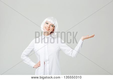Smiling charming young woman standing and holding copyspace on palm