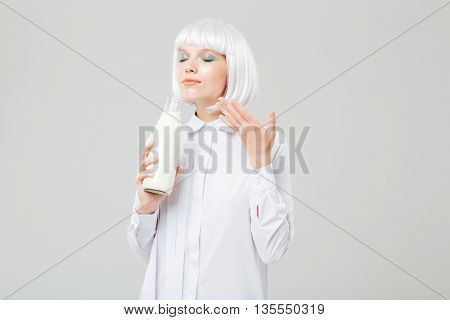 Attractive inspired young woman smelling milk in bottle