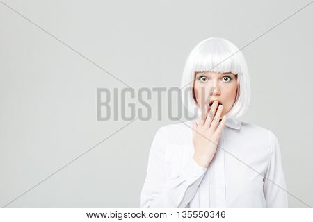 Amazed pretty young woman with blonde hair covered her opened mouth by hand