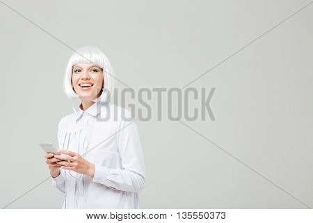 Cheerful charming young woman listening to music from mobile phone
