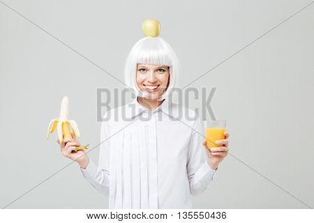 Cheerful young woman with apple on her head holding banana and glass of juice