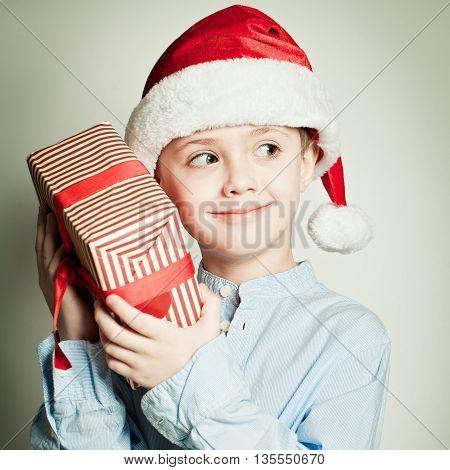 Child in Santa hat holding Christmas gift