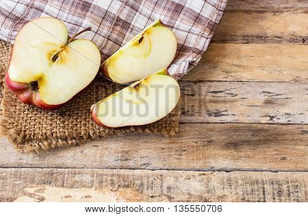 Close up of a sliced red apple on a wooden table. Fresh red apple on old wooden table background. Red apple on wood table. Healthy concept
