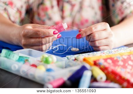 Closeup Of Woman Hands Sewing A Button.