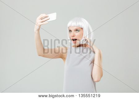 Smiling playful young woman making selfie using smartphone over white background