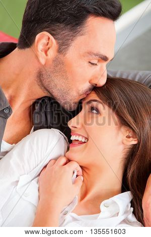 A photo of loving man kissing woman's forehead. Loving young male and female partners spending leisure time. They are at home.