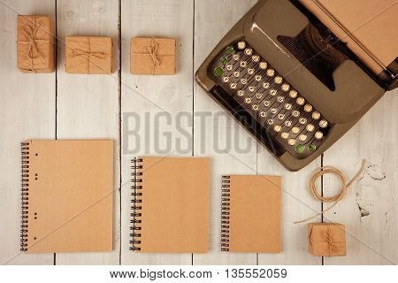 Writer's workplace - vintage typewriter notepads present boxes on the white wooden background