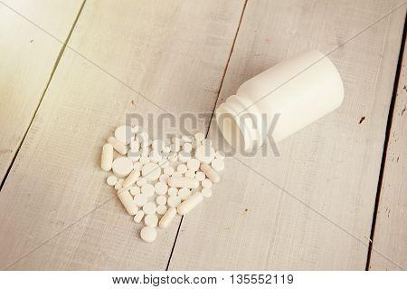 White Heart Of Pills And Capsules On White Wooden Desk