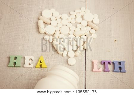 Medical concept in sepia - color HEALTH inscription and white heart of pills and capsules on white wooden desk