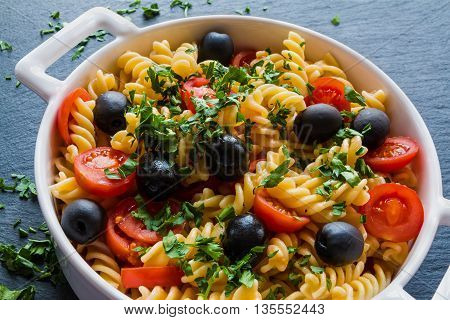 Pasta (fusilli) in white pan on black slate background. Vegeterian cooked with tomatoes black olives garlic and parsley