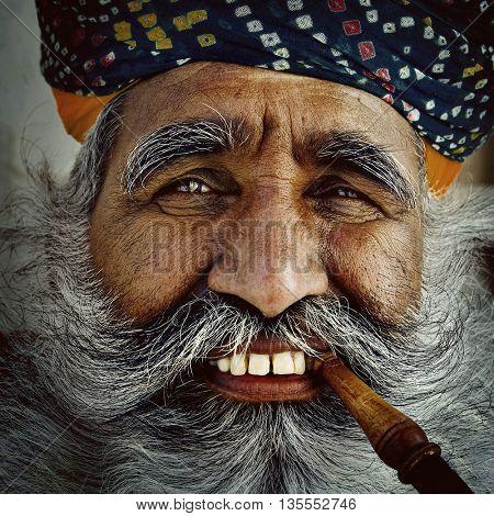 India Man Smoking a Pipe Concept