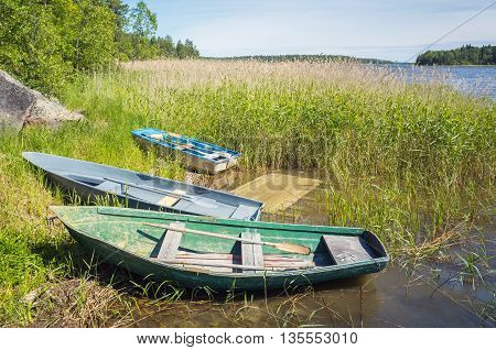 Small Rowboats Lay On The Coast Of Still Lake