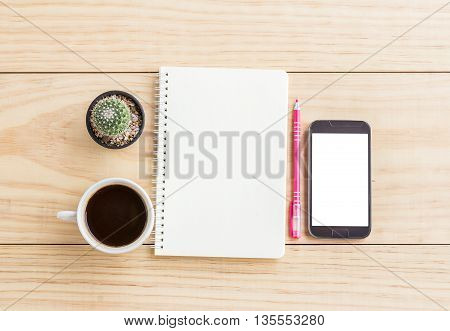 Vintage office desk table with notebookssmart phone pen and a cactus with cup of coffee. Top view with copy space. Business concept