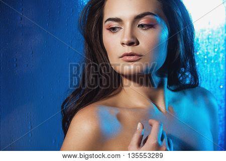 Beauty portrait of beautiful female model on a blue background. Studio shot.