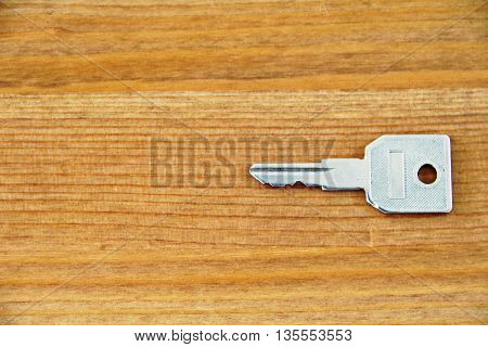 Key on wooden floorboards concept for lock and open any stuff as real estate or things