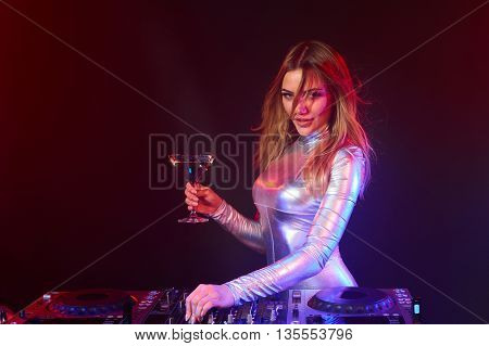 Sexy DJ girl on decks at the party wearing silver coverall holding a glass with cocktail