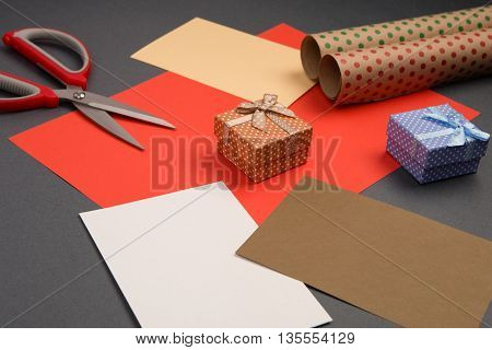 Gift Boxes In Polka Dots, Packaging Paper, Color Paper And Scissors On Grey Background