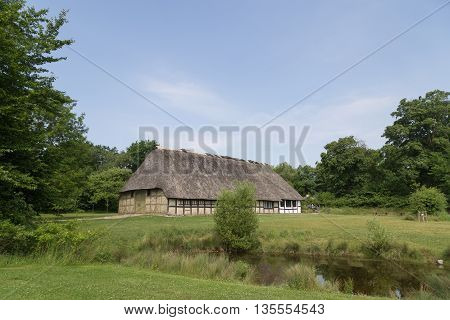 Lyngby, Denmark - June 23, 2016: An ancient danish half-timbered farmhouse with straw roof.