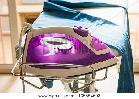 Close up of steam iron on ironing board.