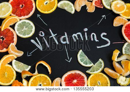 the word vitamins with citrus fruit written on black chalkboard