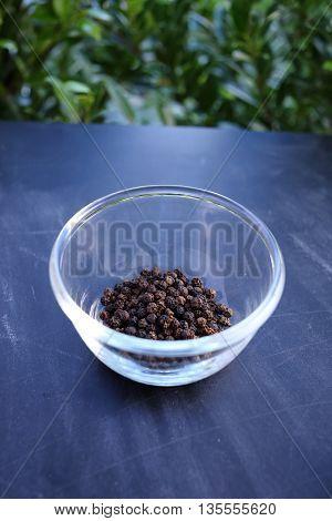 Black pepper in bowl on black background