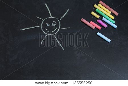 colored chalks on a black blackboard with drawings of the sun