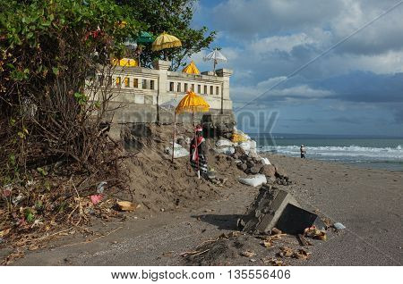 BALI INDONESIA - JUNE 23: A Balinese-Hindu seaside temple damaged by freak waves and severe coastal erosion is protected with sandbags on June 23 2016 at Batu Belig Beach Bali Indonesia.