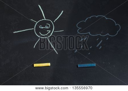 colored chalks on a black blackboard with drawings of a sun and a cloud
